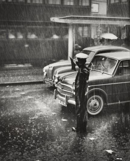 A policeman directs traffic in the rain (1959) | Photographer: Chung Man Lurk